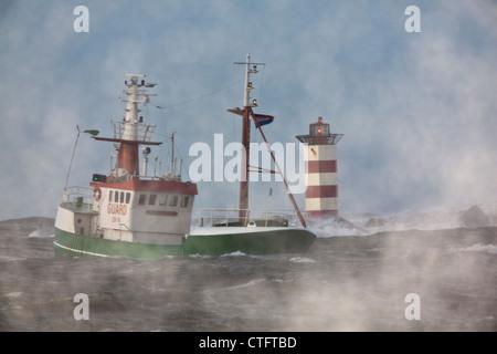 The Netherlands, IJmuiden, Storm. Waves crash against lighthouse or beacon. Ship. - Stock Photo