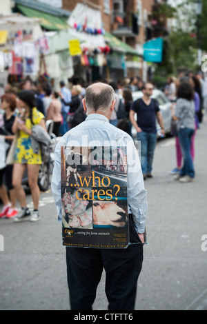 Farm Animal rights campaigner standing with a 'who cares' placard in Portobello Road. London - Stock Photo