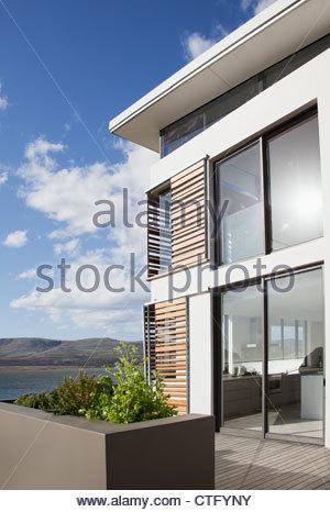 Sun shining on window of modern house overlooking lake - Stock Photo