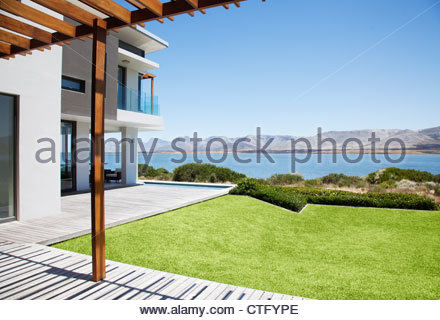 View of lake from patio of modern house - Stock Photo