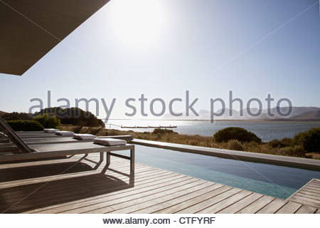 View of sun shining on lake from patio with swimming pool - Stock Photo