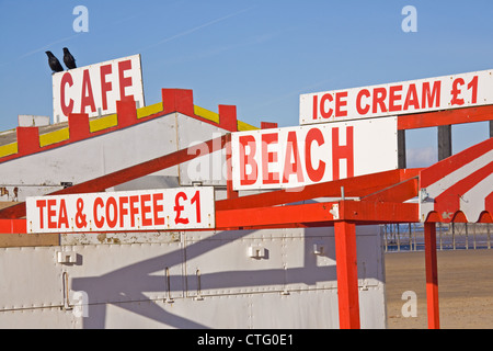 Signs on a deserted English holiday beach advertising the wares of a seaside cafeteria closed for the winter - Stock Photo
