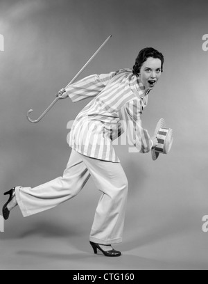 1950s WOMAN IN STRIPED JACKET HOLDING CANE & STRAW HAT SHUFFLING FORWARD IN DANCE - Stock Photo