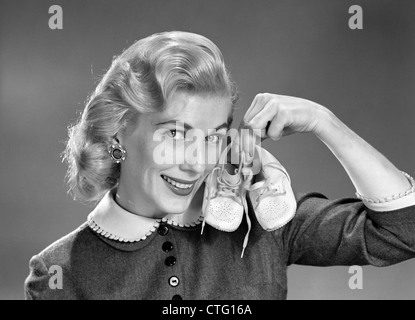 1950s 1960s SMILING BLOND WOMAN COMMUNICATING THAT SHE IS MOTHER TO BE BY HOLDING UP A PAIR OF BABY SHOES LOOKING - Stock Photo