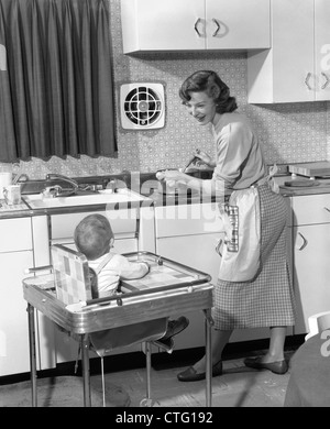 1950s WOMAN MOTHER IN HOME KITCHEN COOKING POT ON STOVE SMILING AT BABY CHILD IN HIGH CHAIR - Stock Photo