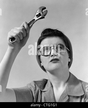 1940s ROSIE THE RIVETER WEARING SAFETY GLASSES HOLDING UP MONKEY WRENCH - Stock Photo
