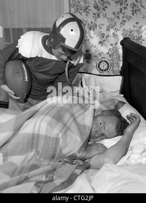 1950s BOY IN FOOTBALL UNIFORM WAKING UP FATHER EARLY IN MORNING - Stock Photo