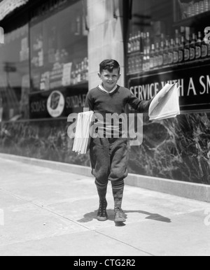 1930s NEWSBOY IN KNICKERS WALKING DOWN STREET HAWKING PAPERS - Stock Photo