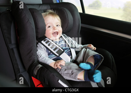 Baby boy in a child safety car seat - Stock Photo