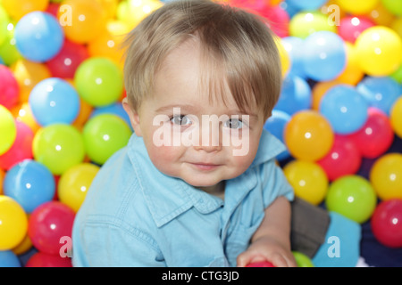 Baby playing in multi coloured balls - Stock Photo