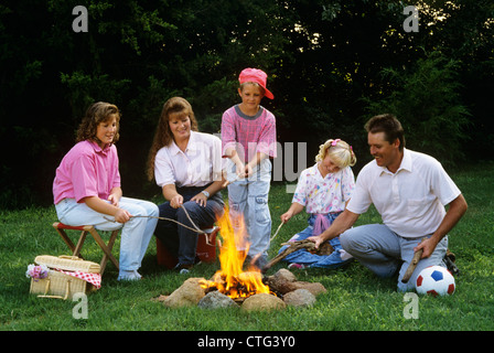 1990s FAMILY ROASTING HOT DOGS ON STICKS OVER CAMPFIRE - Stock Photo