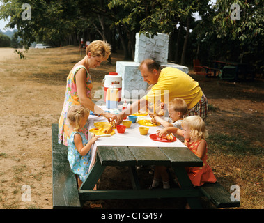 1970s FAMILY EATING AT OUTDOOR PICNIC TABLE - Stock Photo