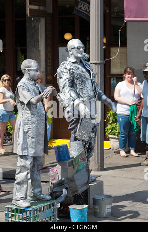 Adult and child street performers painted silver entertain tourists on the sidewalk in the French Quarter of New - Stock Photo