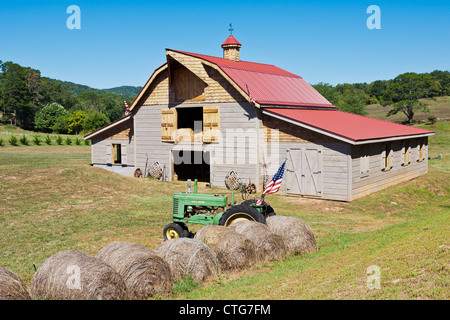 Antique John Deere tractor and an American flag next to rolls of hay on a rural farm near Franklin, North Carolina - Stock Photo
