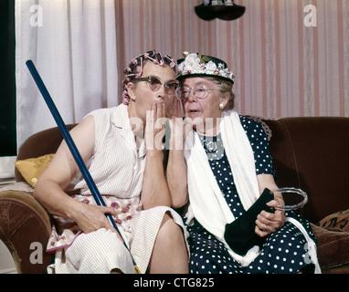 1960s TWO SENIOR OLDER WOMEN SITTING ON SOFA GOSSIPING - Stock Photo