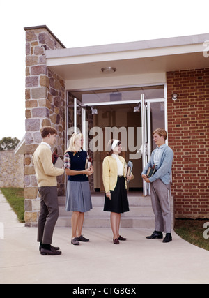 1960s GROUP TEENAGE STUDENTS BOYS GIRLS COUPLES STANDING TALKING AT ENTRANCE TO HIGH SCHOOL CARRYING TEXTBOOKS AND - Stock Photo
