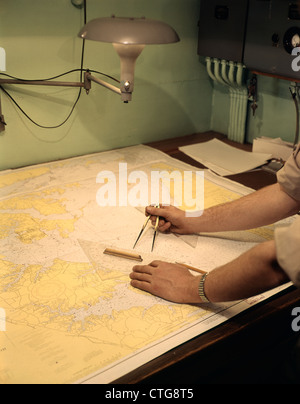 1960s MALE HANDS USING NAUTICAL NAVIGATION TOOLS COMPASS MAP CHART CHARTING A COURSE - Stock Photo