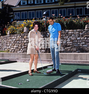 1960s COUPLE MAN WOMAN PLAYING MINIATURE GOLF - Stock Photo