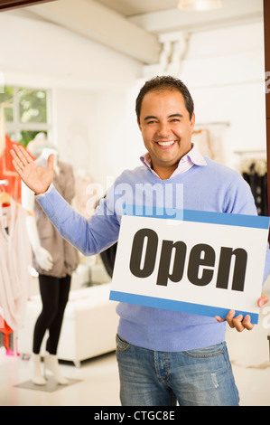 Hispanic man holding open sign in clothing store - Stock Photo