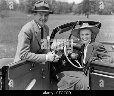 1930s 1940s PORTRAIT COUPLE MAN WOMAN TOGETHER WITH CONVERTIBLE AUTOMOBILE SMILING WEARING HATS LOOKING AT CAMERA - Stock Photo