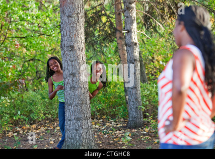 Sisters Playing Hide And Seek In A Park With Their Mother Looking On; Edmonton, Alberta, Canada - Stock Photo