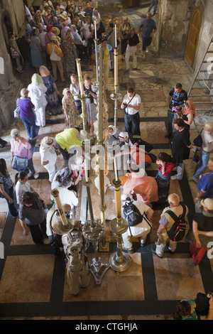 Religious pilgrims and tourists around the Stone of Anointing in the Church of the Holy Sepulchre, Jerusalem, Israel - Stock Photo