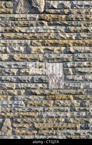 Natural York stone blocks cut & dressed from redundant London paving slabs & reused in external skin of new house - Stock Photo