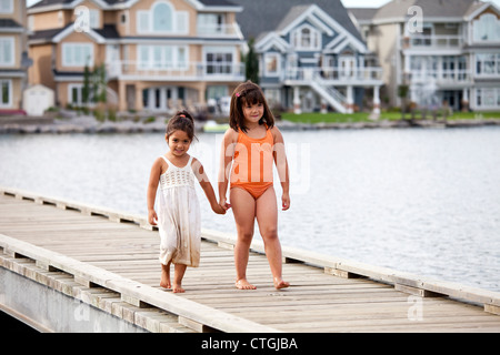 Two Sisters On A Pier At A Residential Lake Area; Edmonton, Alberta, Canada - Stock Photo