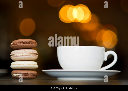 A stack of macaroons next to a cup of coffee. - Stock Photo