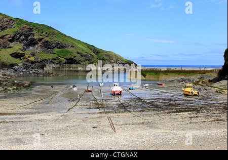 Landscape picture of Port Isaac harbour in Cornwall at low tide showing a number of fishing boats. - Stock Photo