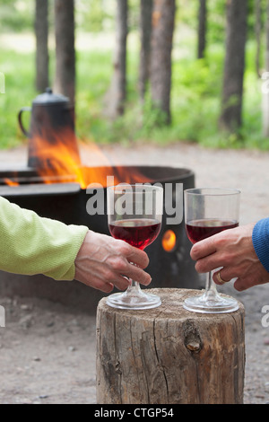 A Couple Holding Wine Glasses On A Block Of Wood With A Fire Pit Burning In A Campground; Waterton, Alberta, Canada - Stock Photo