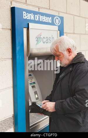 Cork, County Cork, Ireland. Elderly man withdrawing money from Bank of Ireland cash dispenser. - Stock Photo