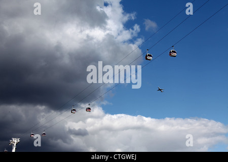 Emirates Air Line Cable Cars and an Aeroplane in a Stormy Sky - Stock Photo