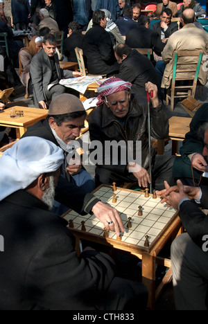 Men concentrated on a board game at the Guhrukculer Hani Square in Sanliurfa ( Urfa ), Turkey - Stock Photo
