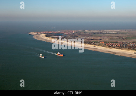 The Netherlands, Westkapelle, Aerial of beach at low tide. Cargo ships on river called Western Scheldt on their - Stock Photo