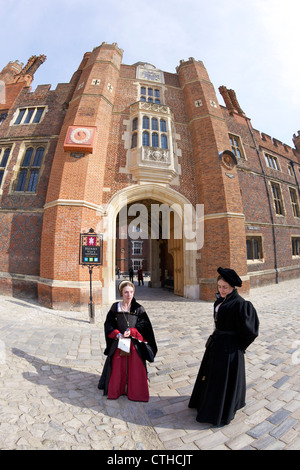 Actresses in costume performing in front of the Anne Boleyn's Gate, Base Court, Hampton Court Palace, London, Surrey, - Stock Photo