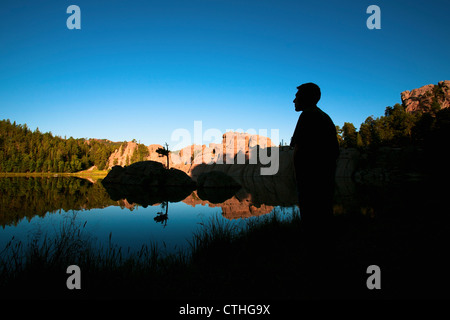 Silhouette Of A Young Man Standing At The Water's Edge Of Sylvan Lake; Black Hills, South Dakota, United States - Stock Photo