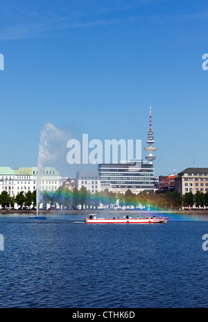 Tourist boat passing the fountain on Binnenalster Lake at Hamburg, rainbow in  spraying water - Stock Photo
