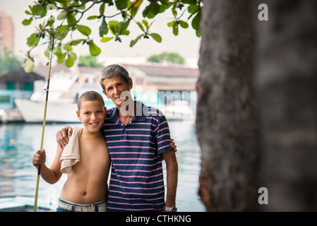 Family portrait with happy boy and grandfather hugging and smiling at camera after fishing near river - Stock Photo