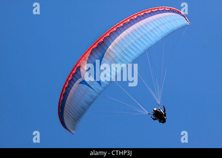 Paraglider in blue sky at Bobs Peak, Queentown, Otago, South island, New Zealand - Stock Photo