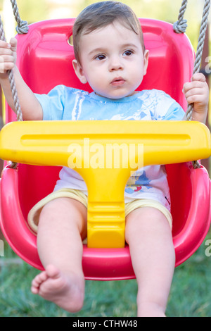 Close Up Of 9 Month Old Baby Boy In A Swing Outdoors