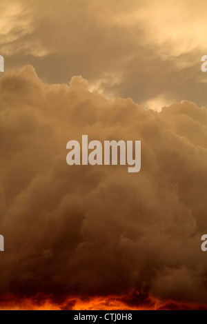 Detail of a cloud lit from underneath by the setting sun, giving the impression of being afire. - Stock Photo