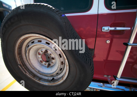 Flat tire mounted on the back of a conversion van. - Stock Photo