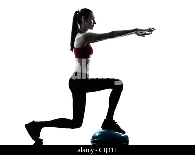 one caucasian woman exercising bosu balance ball trainer in silhouette studio isolated isolated on white background - Stock Photo