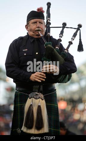 A fireman plays bagpipes - Stock Photo