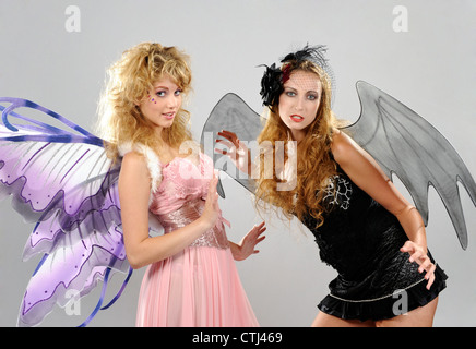 Two young women dressed as good and evil faeries with wings - Stock Photo