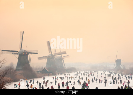 Dutch ice skaters in front of five of the 19 windmills at Kinderdijk in the Alblasserwaard polder, Holland, The - Stock Photo