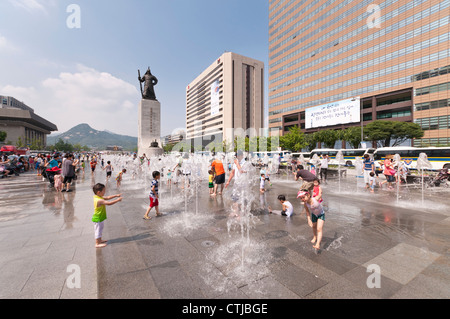 Children having a good time with fountain in Gwanghwamun Square in summer, Seoul, Korea - Stock Photo