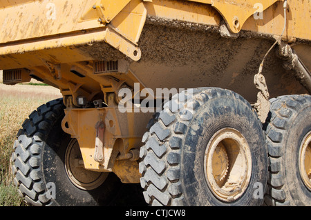 Large yellow mining truck with huge tires at construction site - Stock Photo