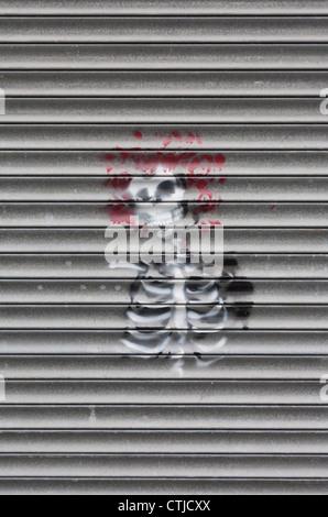 Street art skeleton with red hair graffiti sprayed on metal shutter